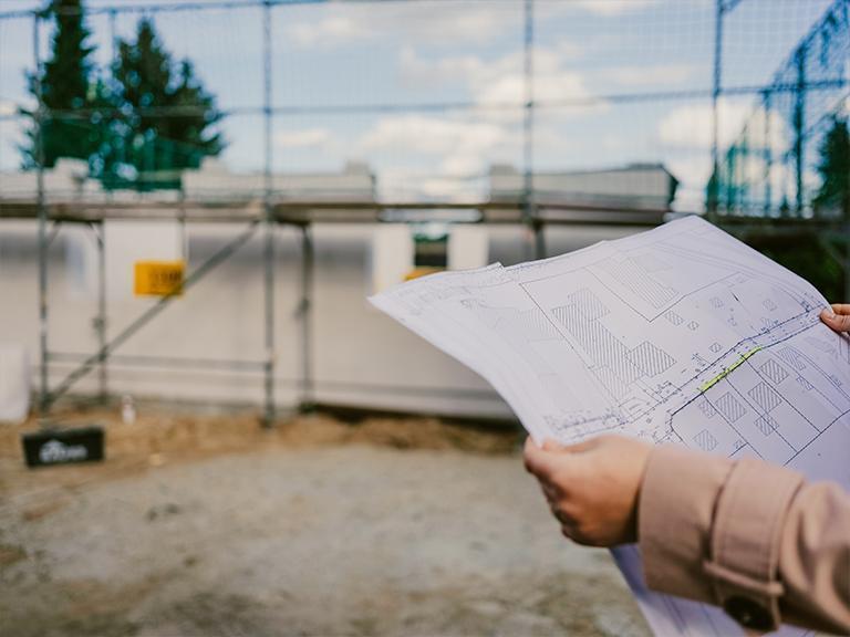 Osoba trzymająca plan budowy